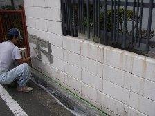 ブロック塀の目地をカチオン系セメントフィーラーで均一に平らにしている様子