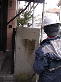 コンクリート塀にこびりついた苔を水洗い除去する風景1