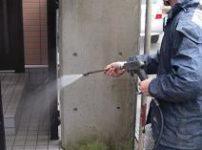 コンクリート塀にこびりついた苔を水洗い除去する風景2